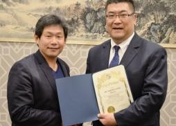 核桃市市議員秦振國向中國北方畫苑總經理吳中洋頒賀狀